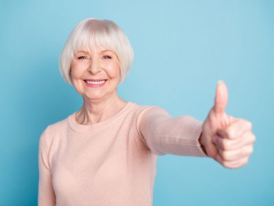 Portrait of lovely lady showing thumb up smiling wearing pastel pullover isolated, over blue background