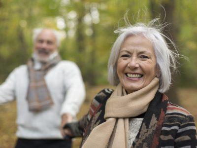 Portrait happy senior woman in autumn park